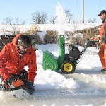 clearing snow and cutting ice to gain access to lake