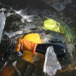 diver breaking ice to emerge from lake
