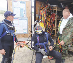 Divers Robert Rozzi (left) and Larry Weinmann (right) assist Erik Toews as he prepares to enter the water.