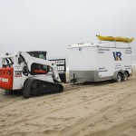 Bobcat hauling dive trailer to a new beach location