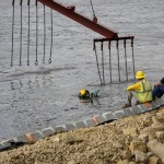 diver assists with underwater placement as crane lowers revetment mats